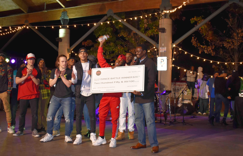 Night Market Founder, Benito Lubazibwa Presents check to Dance Off Contest winner Todd Belin